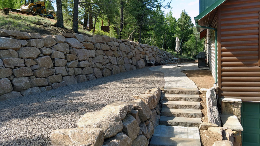 Boulder retaining wall and concrete steps with paver to create more usable outdoor space in Divide Colorado