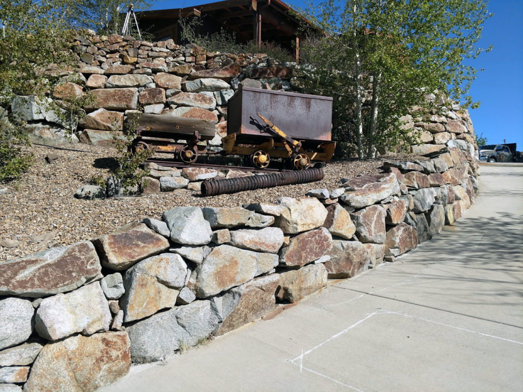 Boulder retaining wall with antiques and planting in Cripple Creek CO