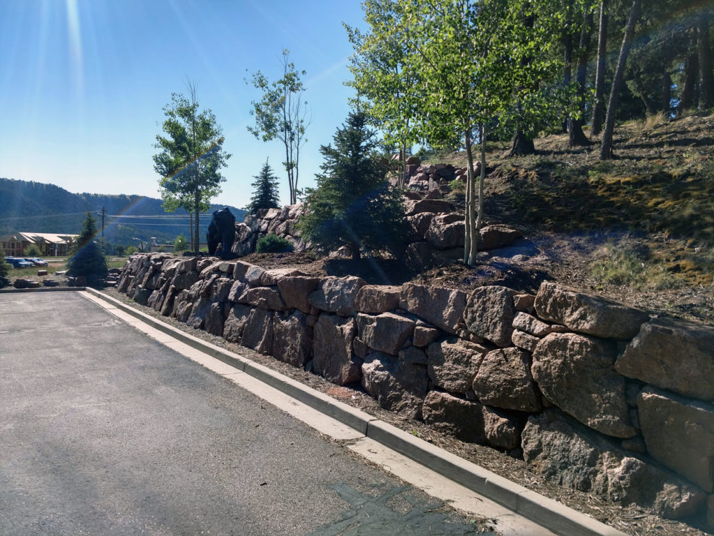 Multi-tier boulder retaining wall with landing and plantings in Woodland Park CO