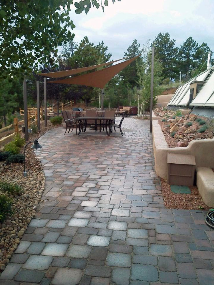 Paver patio with xeriscape planters and shade sails in Florissant CO